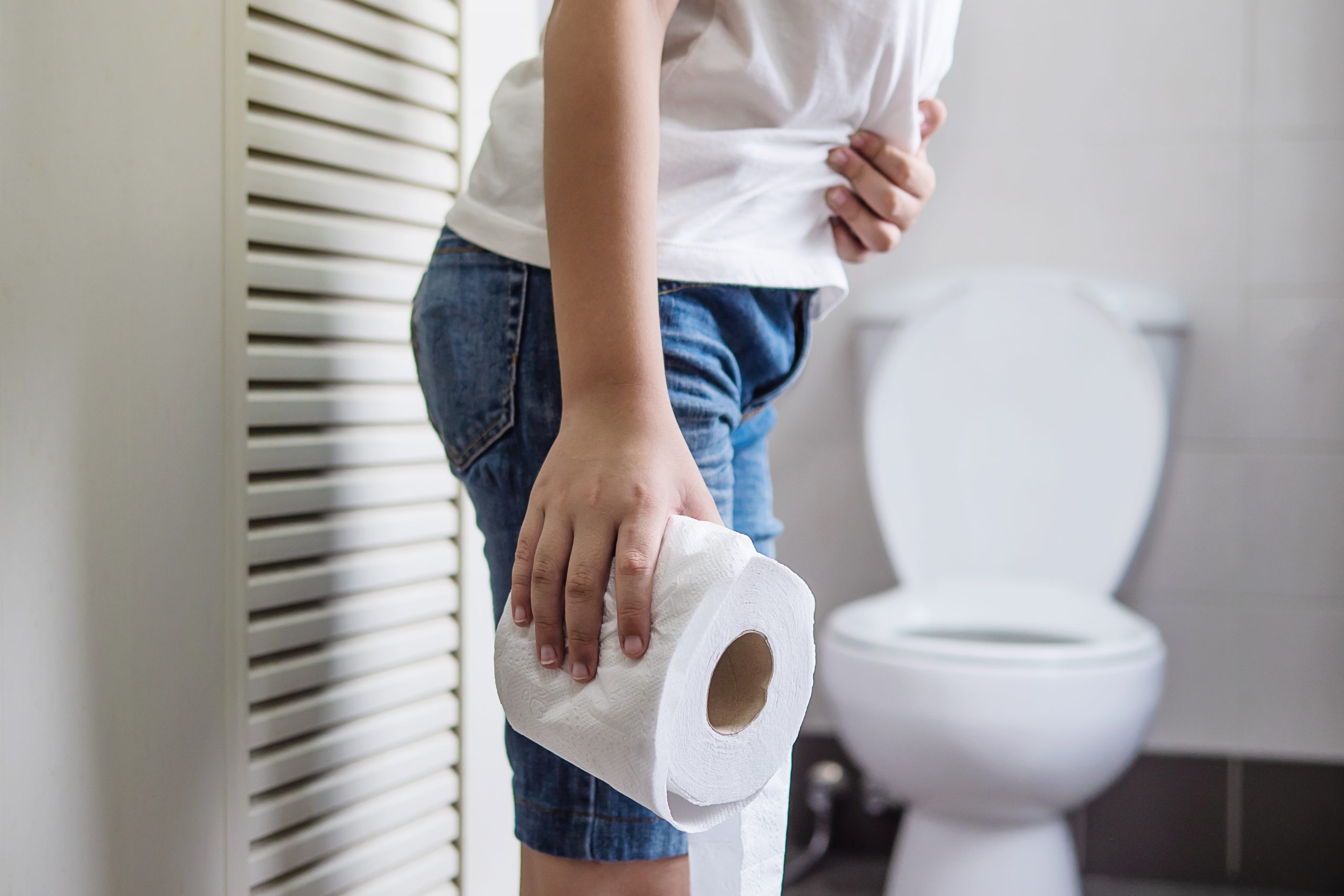 asian boy sitting toilet bowl holding tissue paper health problem concept scaled