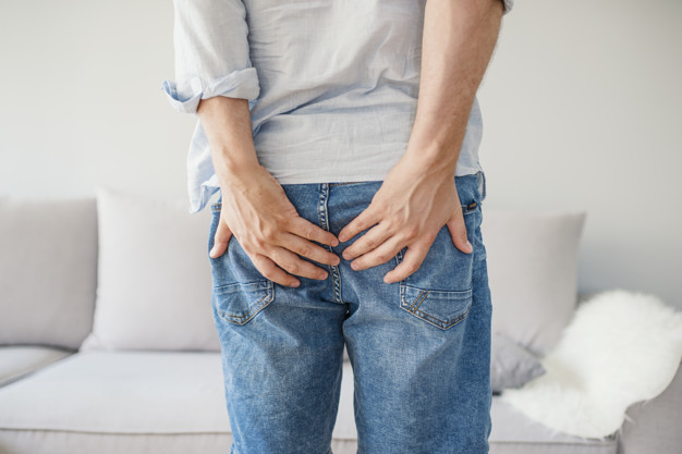 man holding his bottom pain isolated grey 1391 2303