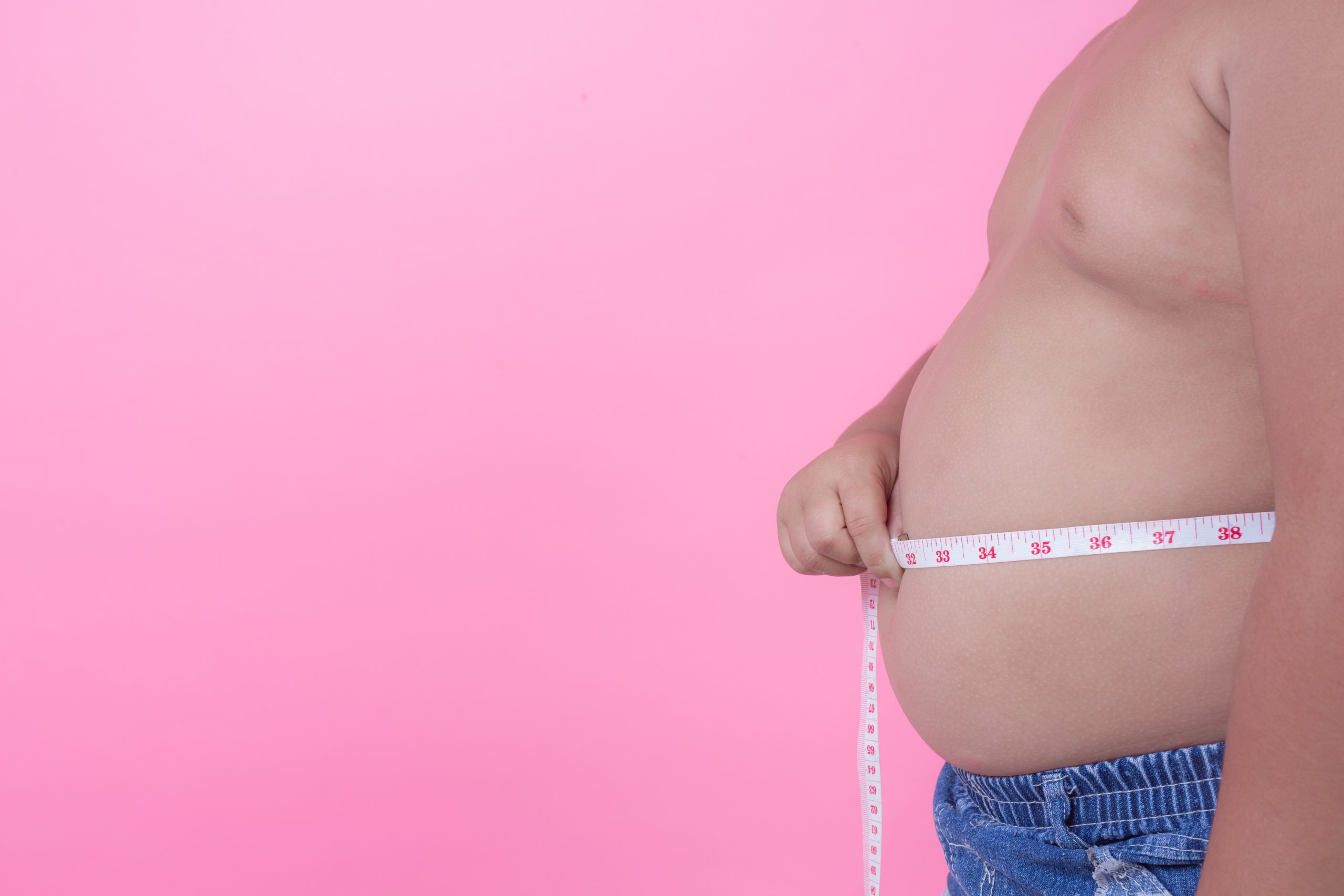 obese boy who is overweight pink background scaled
