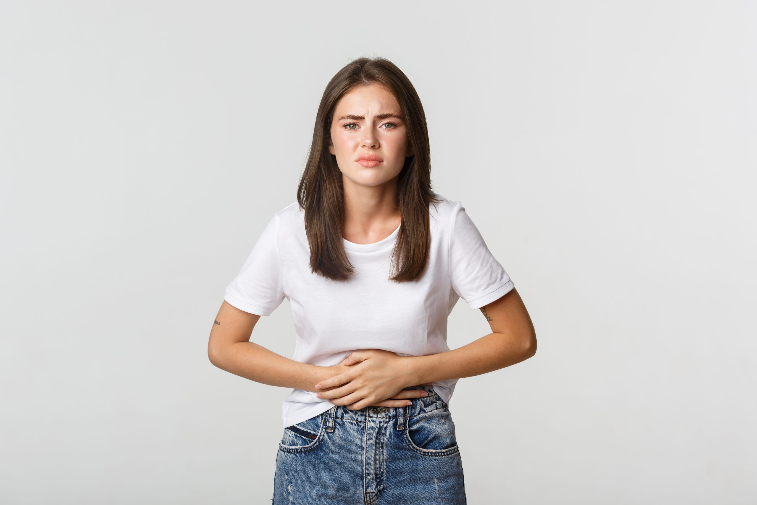 woman having stomach ache bending holding hands belly discomfort from menstrual cramps girl feeling nauseous scaled